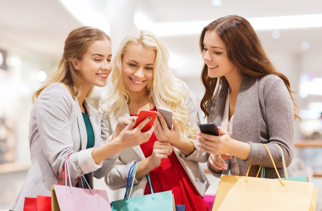 Three happy young women with shopping bags in mall looking at their smartphones